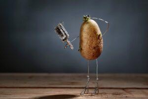 Symbolbild: Runzelige Kartoffelfigur schaut in Spiegel